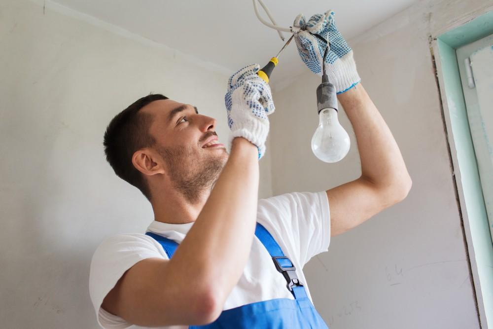 elektryk montuje oświetlenie