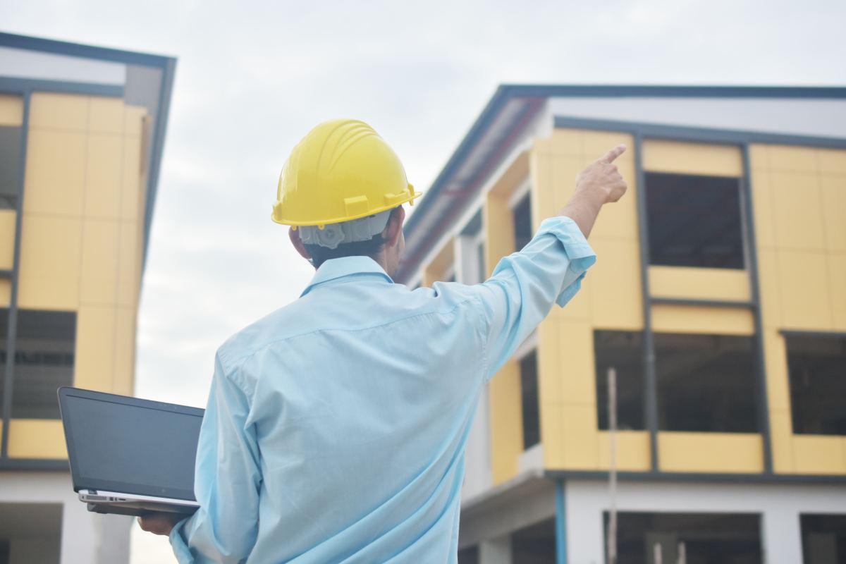 kierownik, inżynier na placu budowy wskazuje na budynek palcem