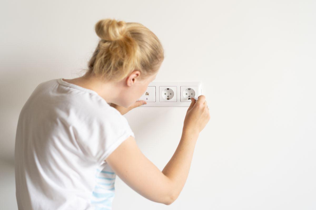 kobieta robi coś przy gniazdku elektrycznym na ścianie w mieszkaniu