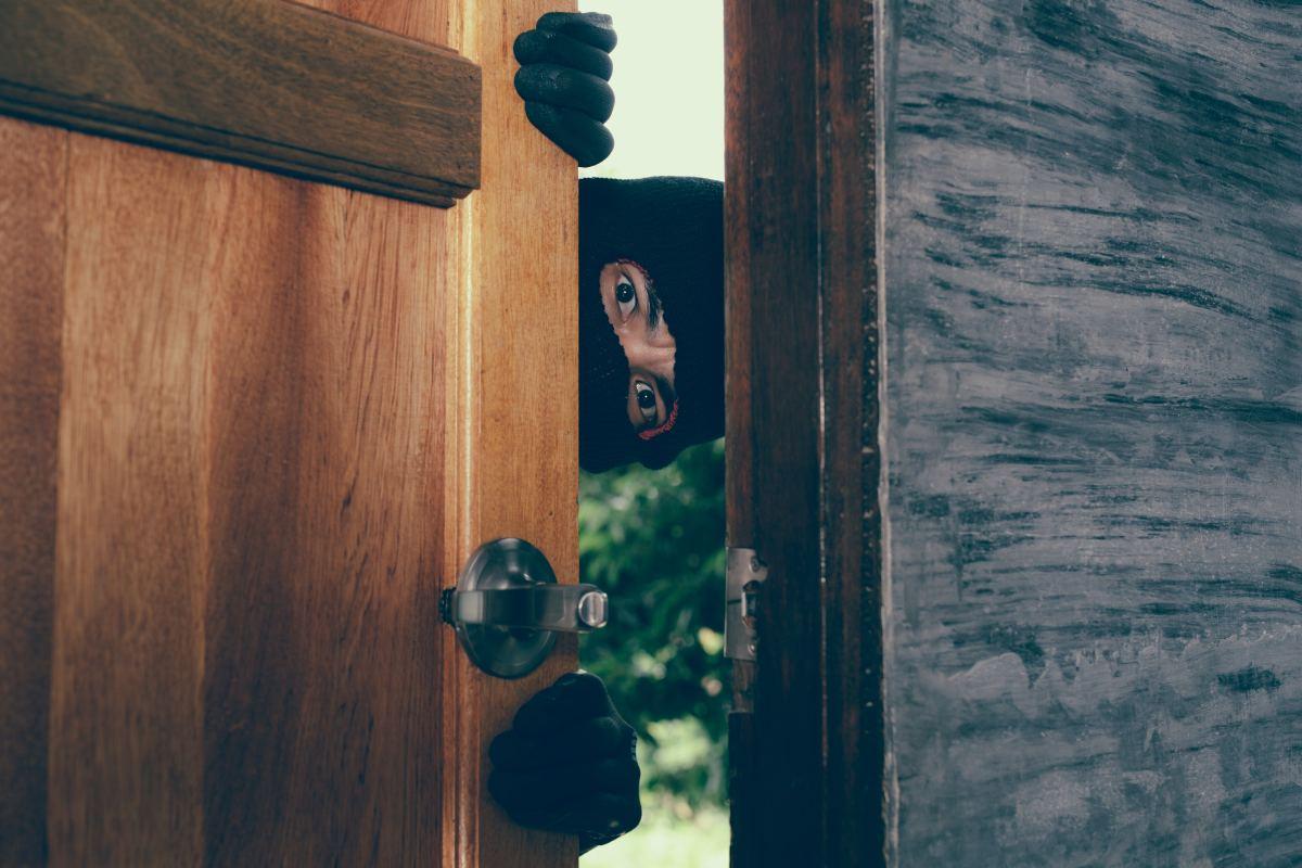 złodziej patrzy przez szparę w drzwiach
